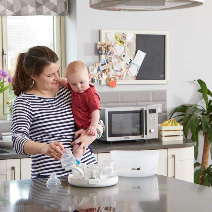 mum-holding-baby-in-kitchen-filling-micro-steam-steriliser-with-bottles