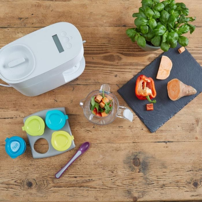 Quick-Cook-Baby-Food-Maker-steamer-blender-top-down-shot-on-bench-with-pop-up-freezer-trays-pots-and-tray-and-ingredients-including-sweet-potato-basil-and-red-pepper